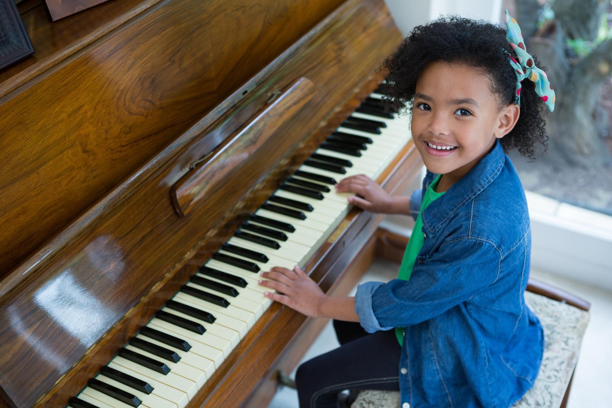 Adorable girl playing piano